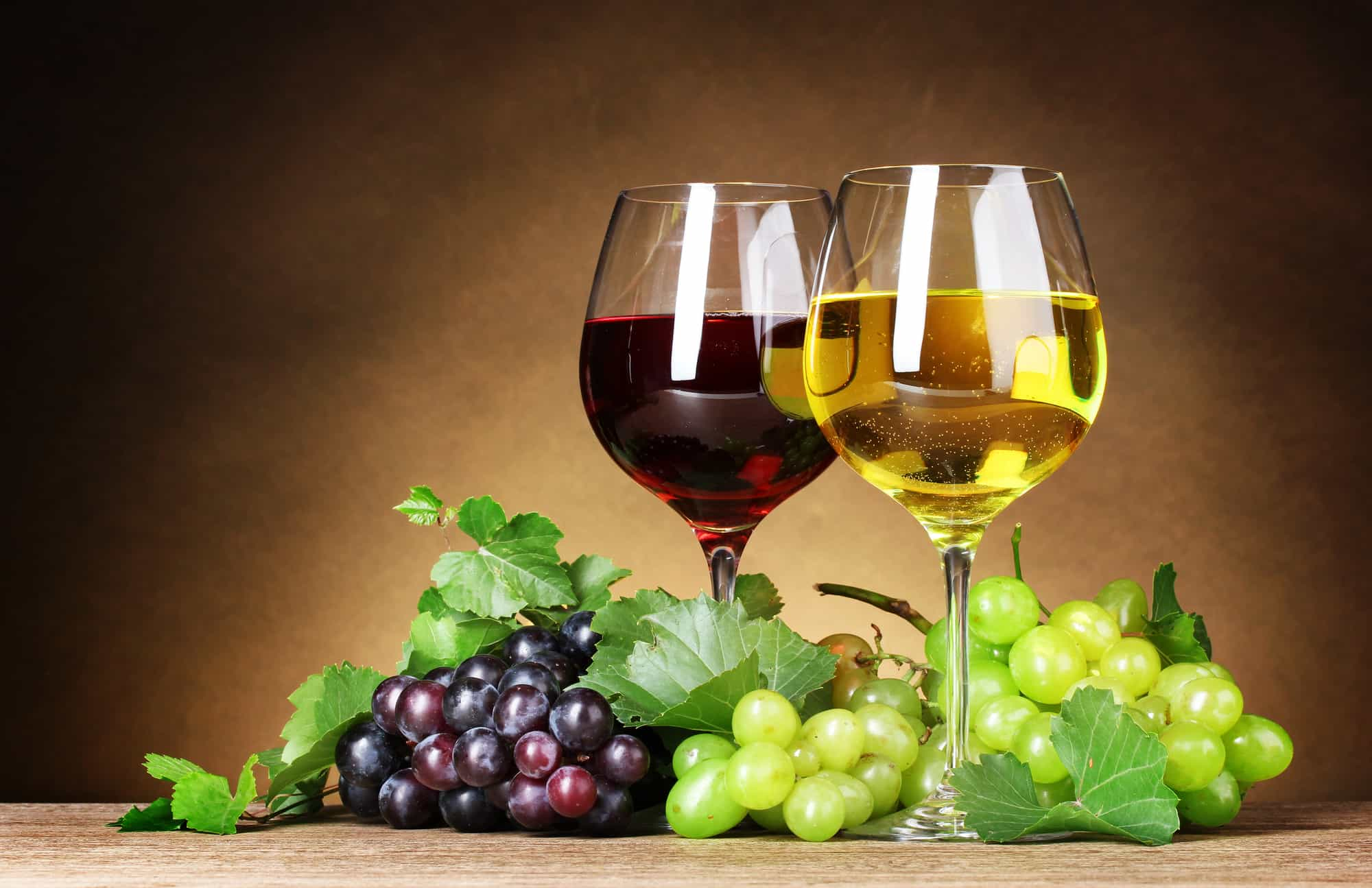 Glasses of wine and grapes on yellow background