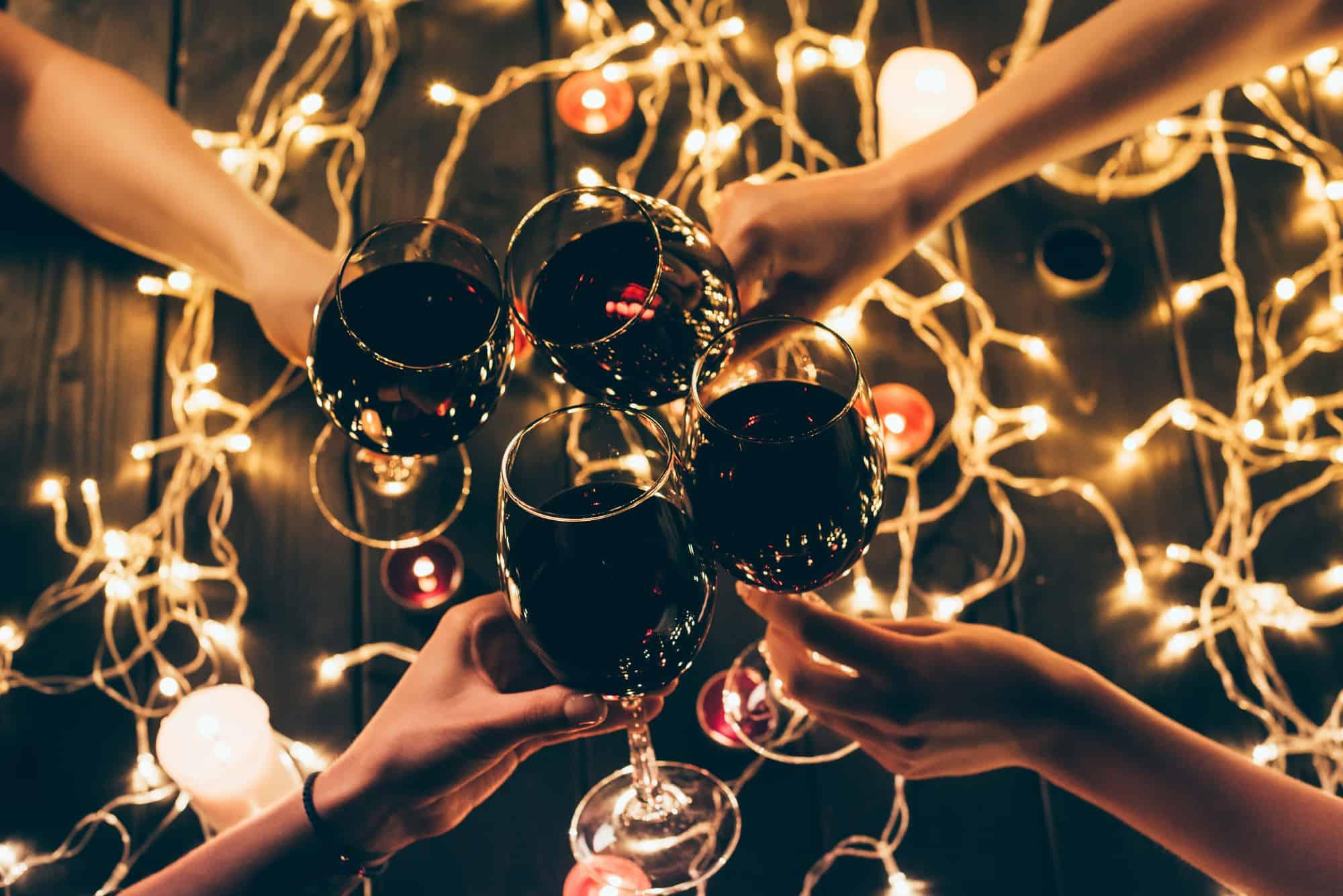 friends sharing wine around christmas lights