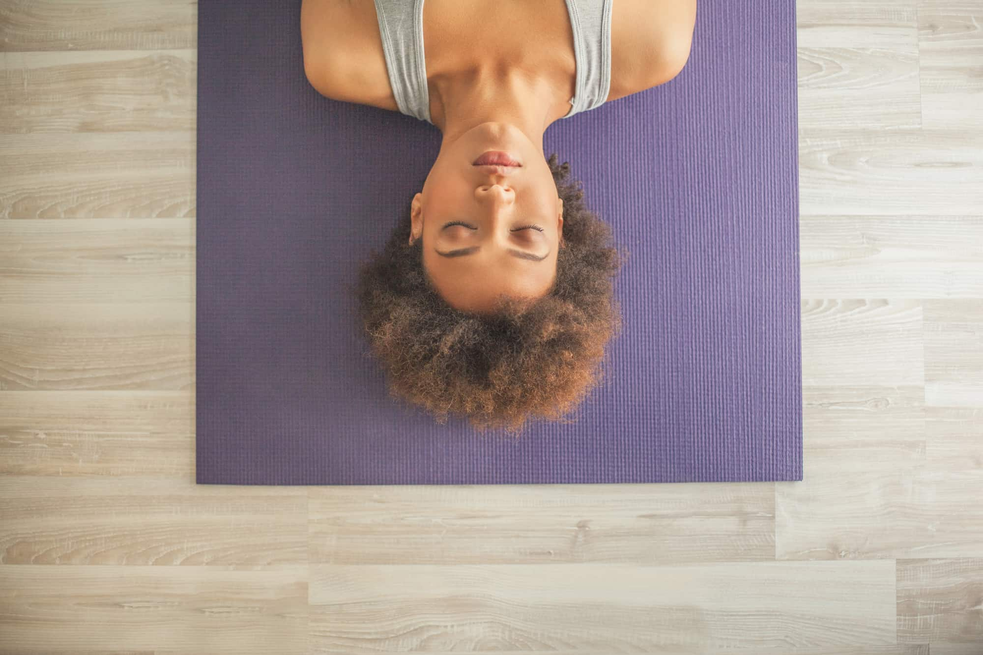 Indoor high-angle shot of woman lying on a yoga mat with her eyes closed
