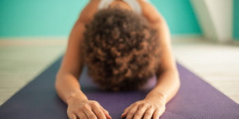 Indoor shot of an African woman doing a forward bend yoga exercise.