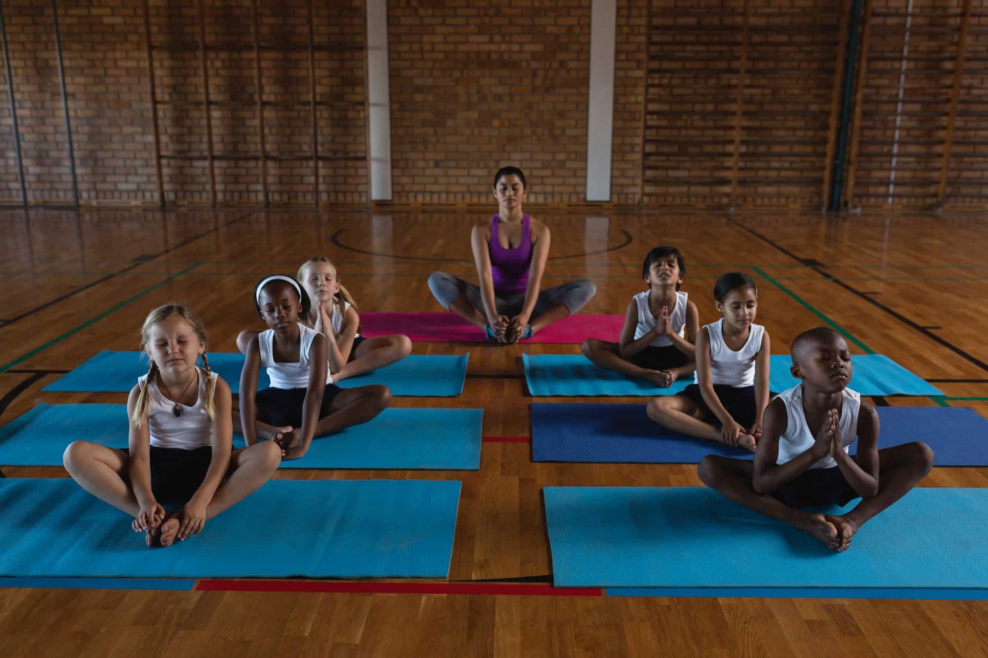 Children sitting on yoga mats meditating