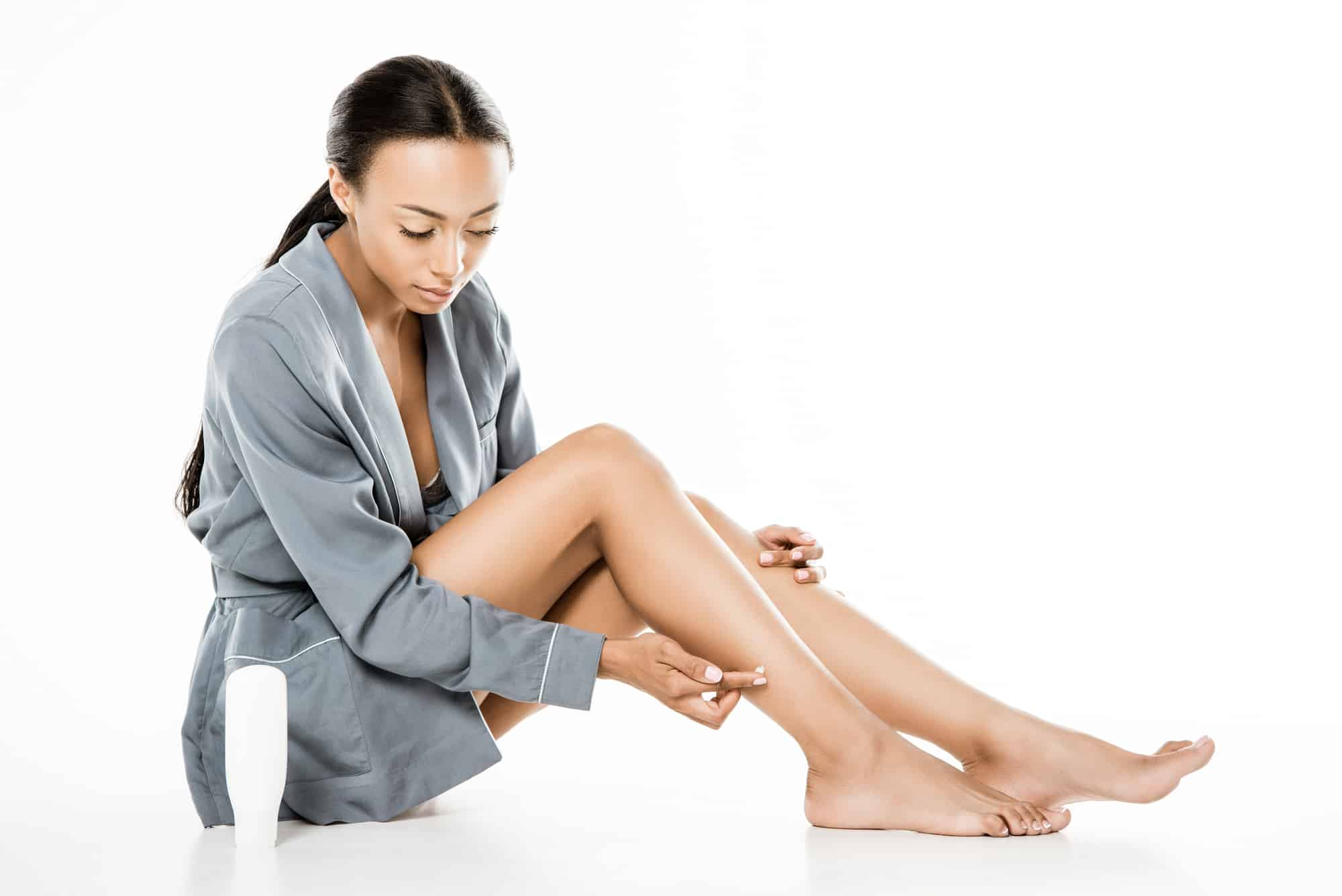 woman of color putting lotion on her dry skin on her legs