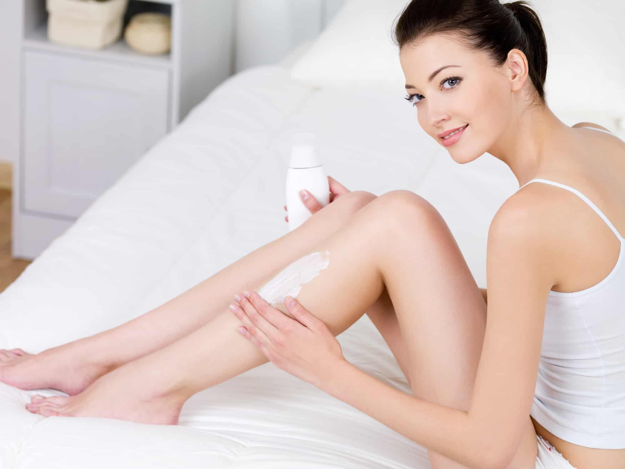 Young beautiful woman applying body lotion on her attractive legs indoors