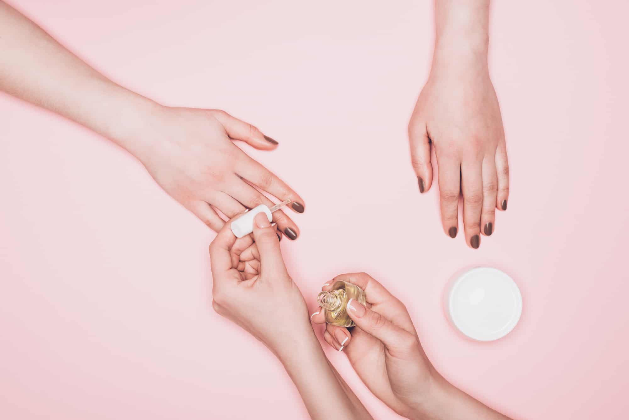 woman doing other woman's nail on a pink background