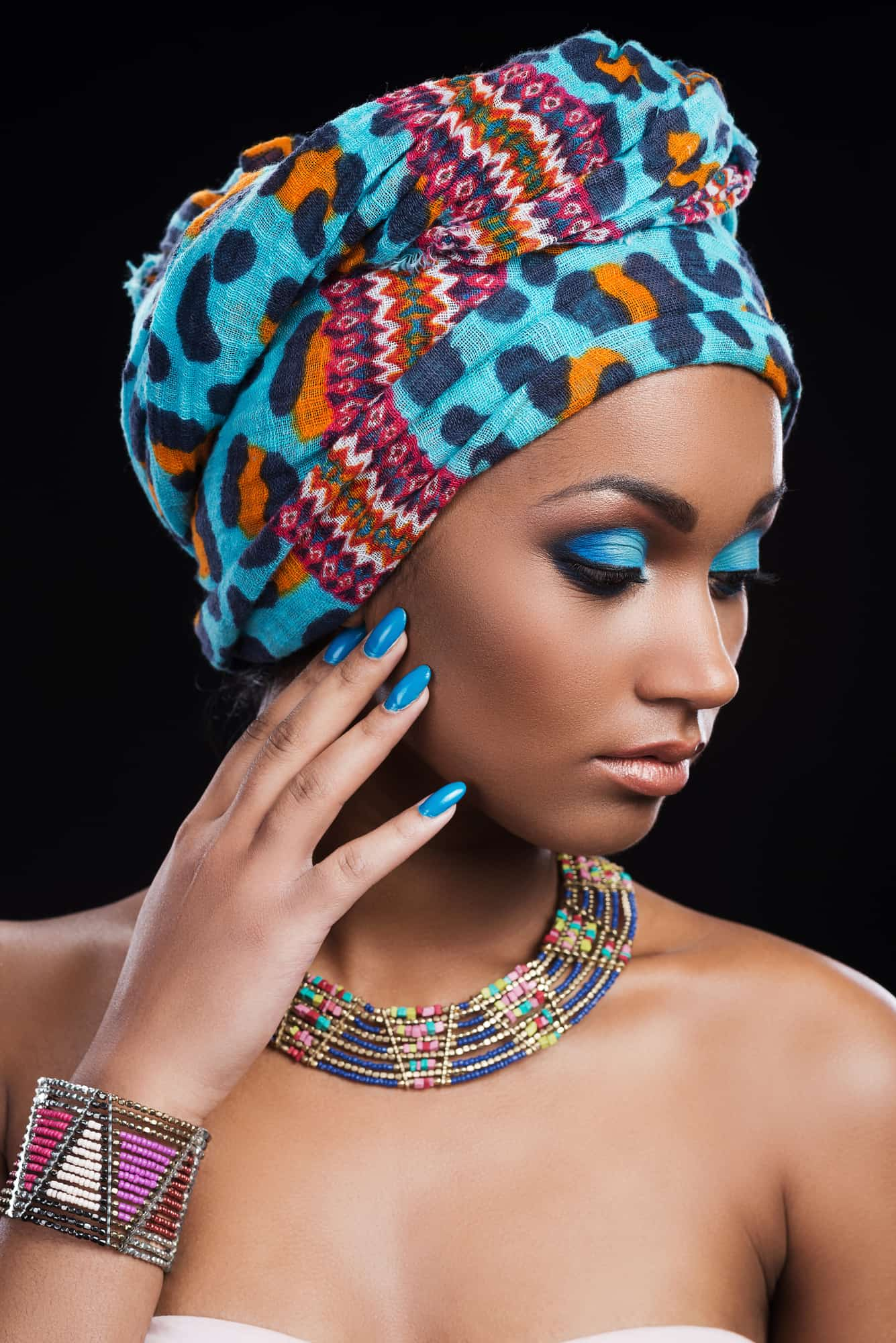 Confident in her perfect look. Beautiful African woman wearing a headscarf and necklace looking away and touching her face
