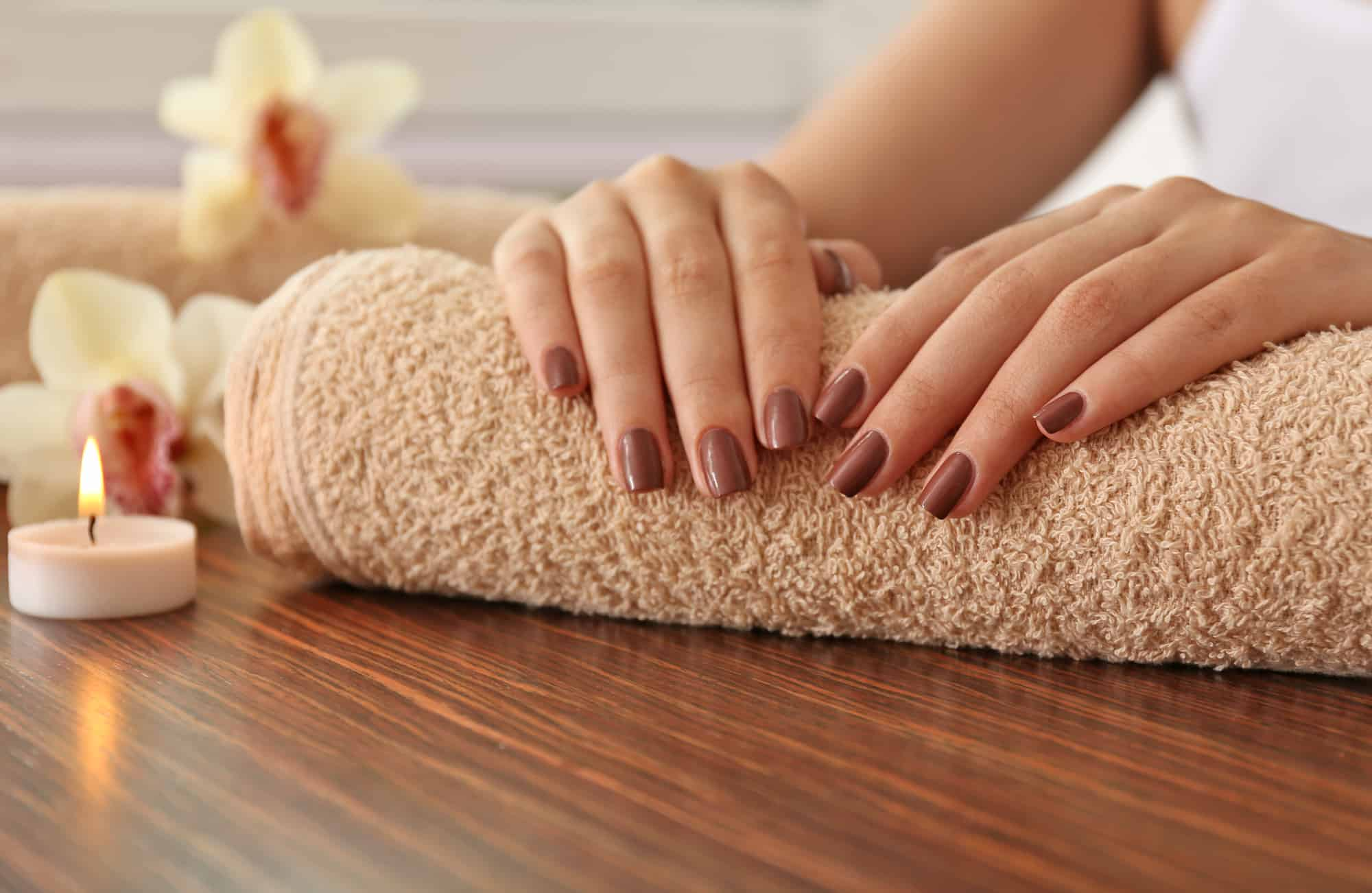 Female brown manicure on towel, closeup