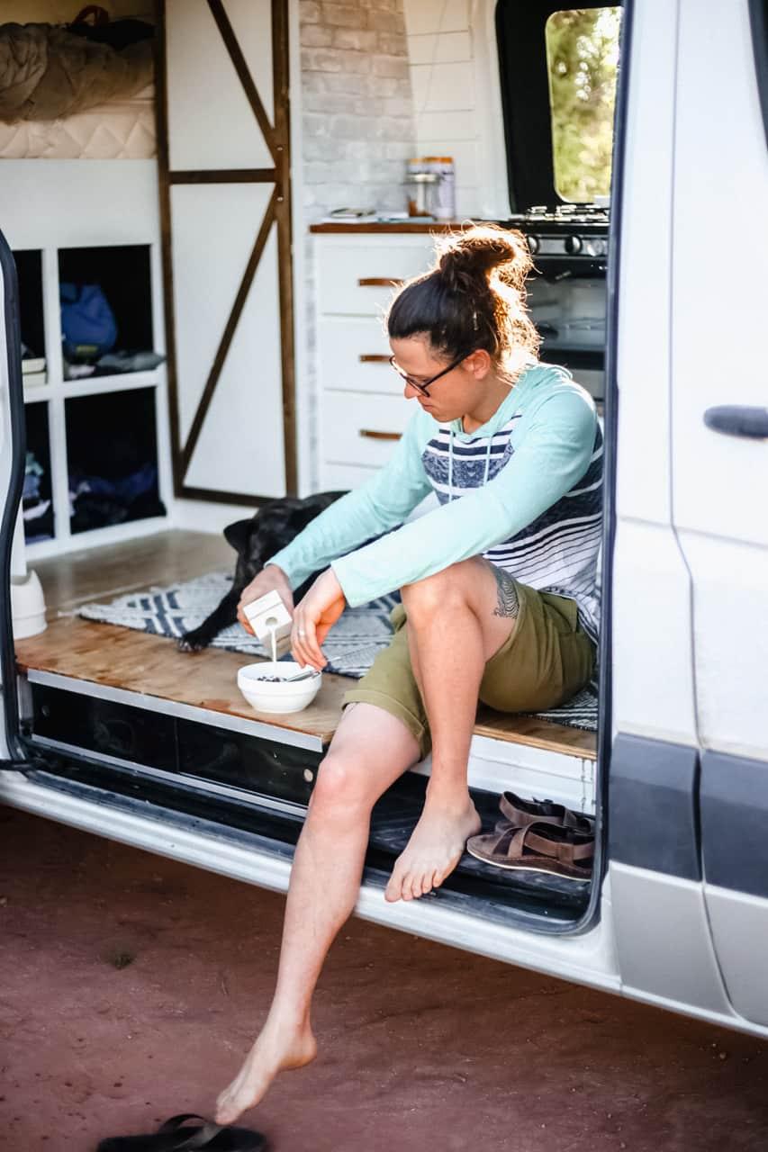 Ashlee Rowland's husband eats breakfast in sustainable van