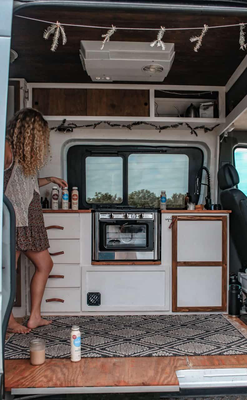 ashlee rowland cooking in her sustainable van