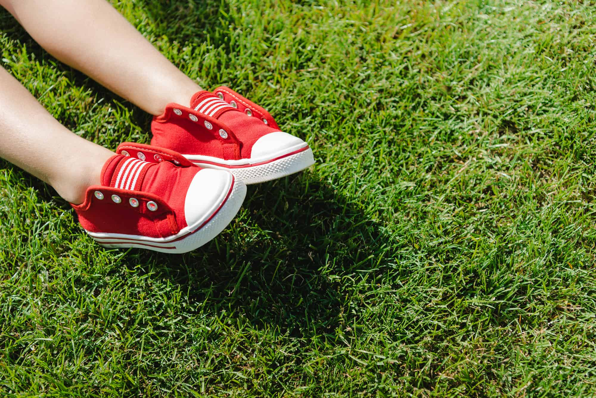 small boy wearing red shoes laying on grass treated as organic land care