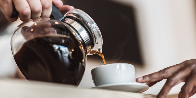 filling up a cup of coffee at a cafe