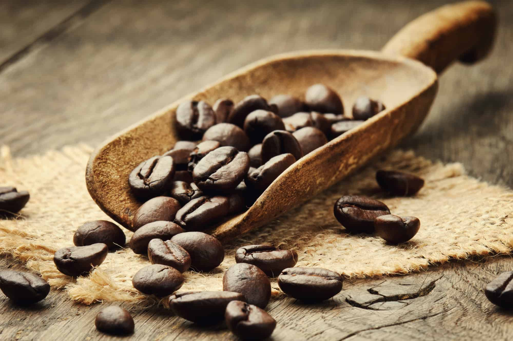 Coffee beans in an old wooden scoop