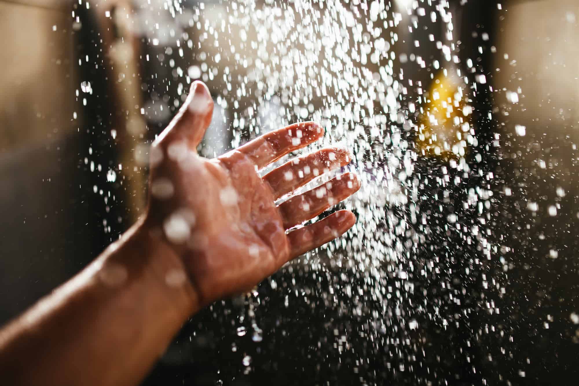 A man's hand in a spray of water in the sunlight against a dark background. Water as a symbol of purity and life