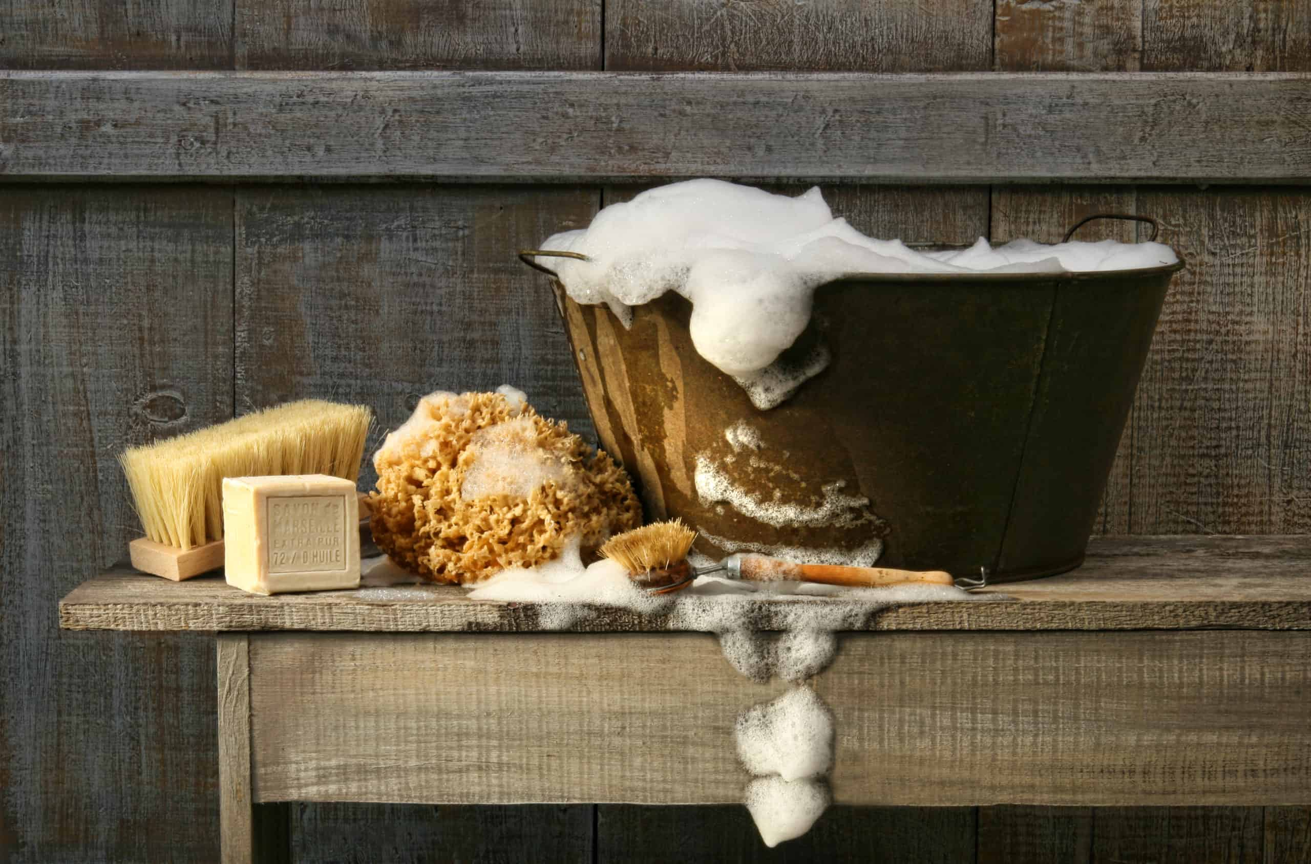 Old wash tub with soap on rustic bench
