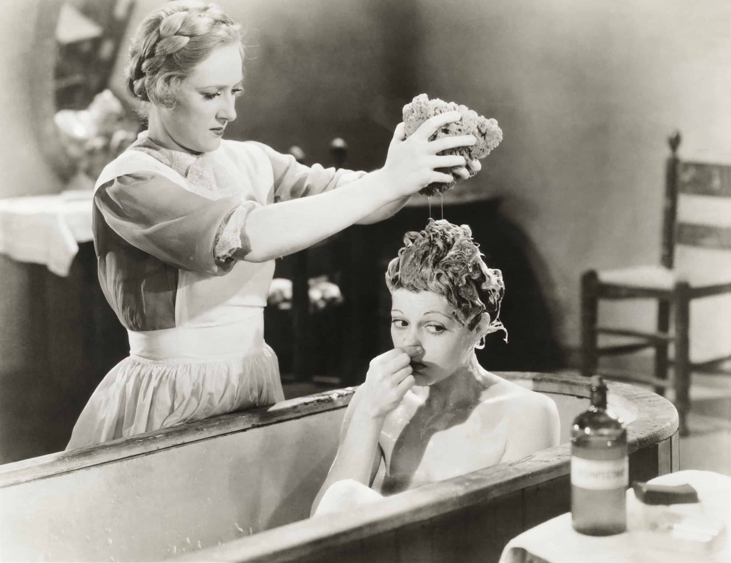 Woman giving other woman bath in tub vintage