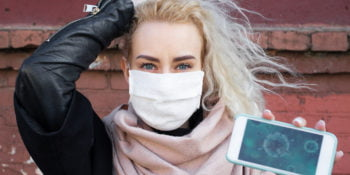 The girl shows on the phone the structure of the virus in a protective medical mask