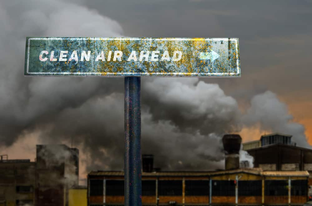 Clean air ahead slogan on the road sign in front of the polluting factory