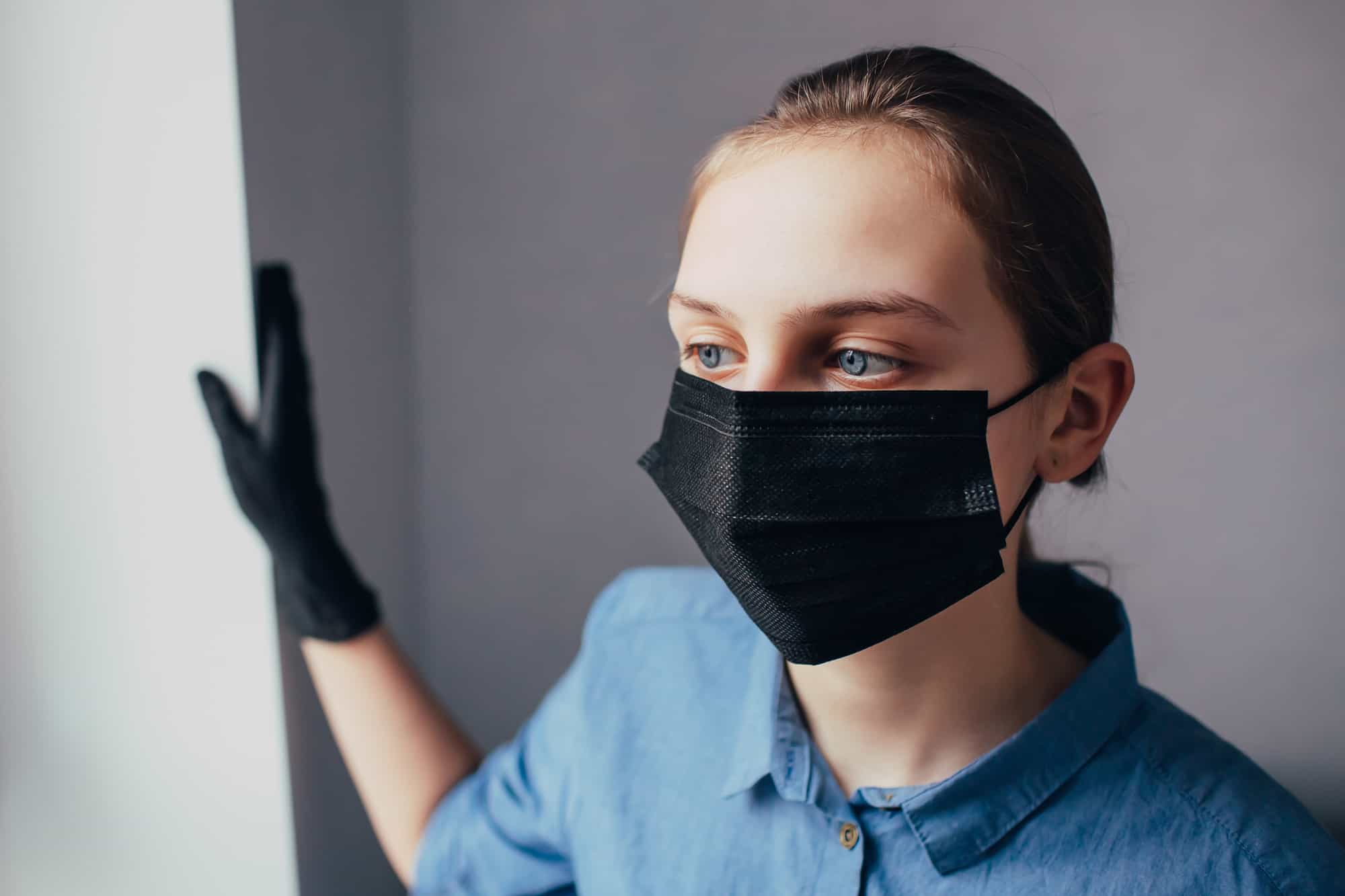 a nurse in a black mask and medical gloves looks away and thinks how to protect people from the coronavirus. Doctor in clinic thinks