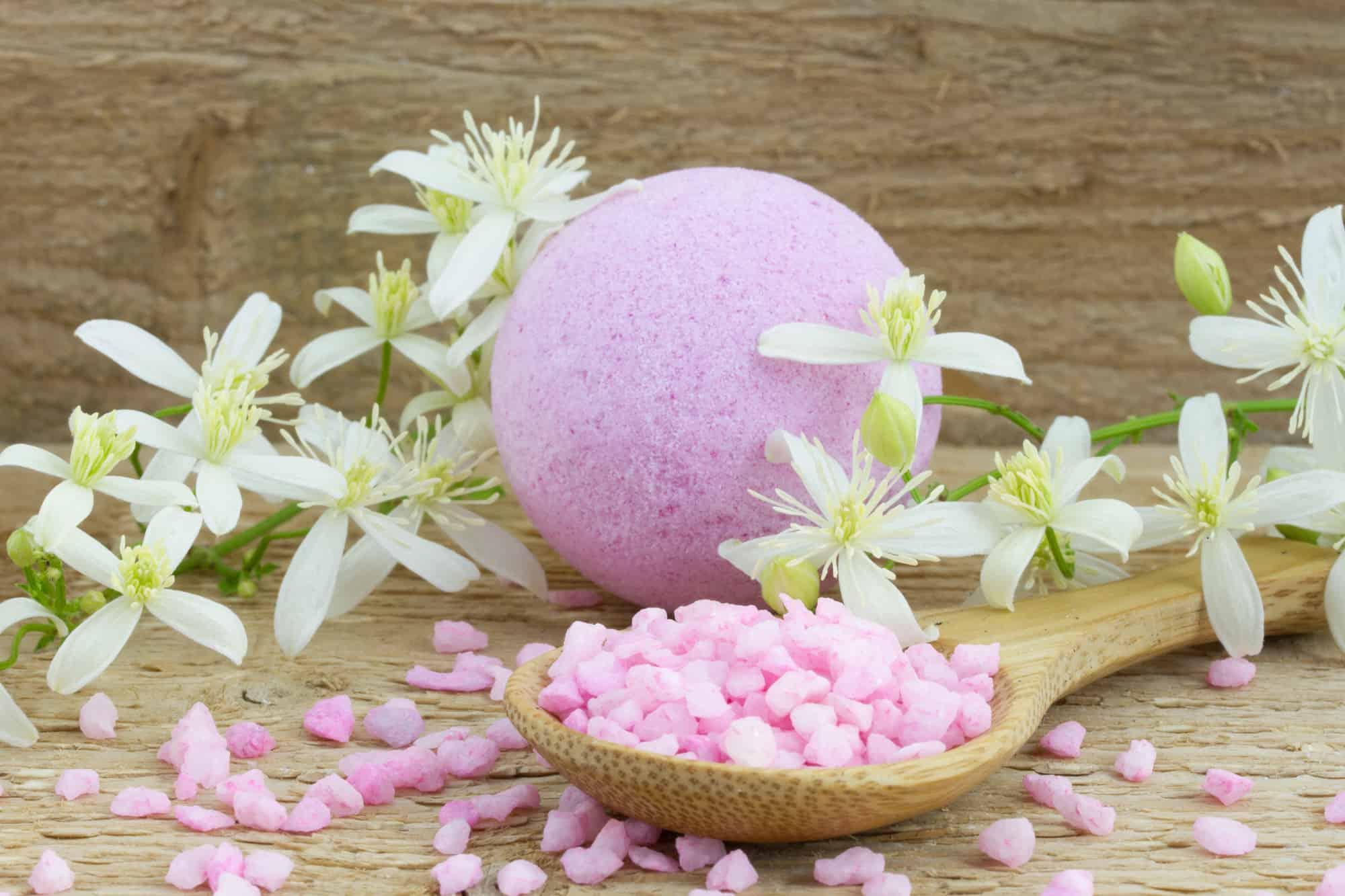pink bath bomb and bath salt on a spoon