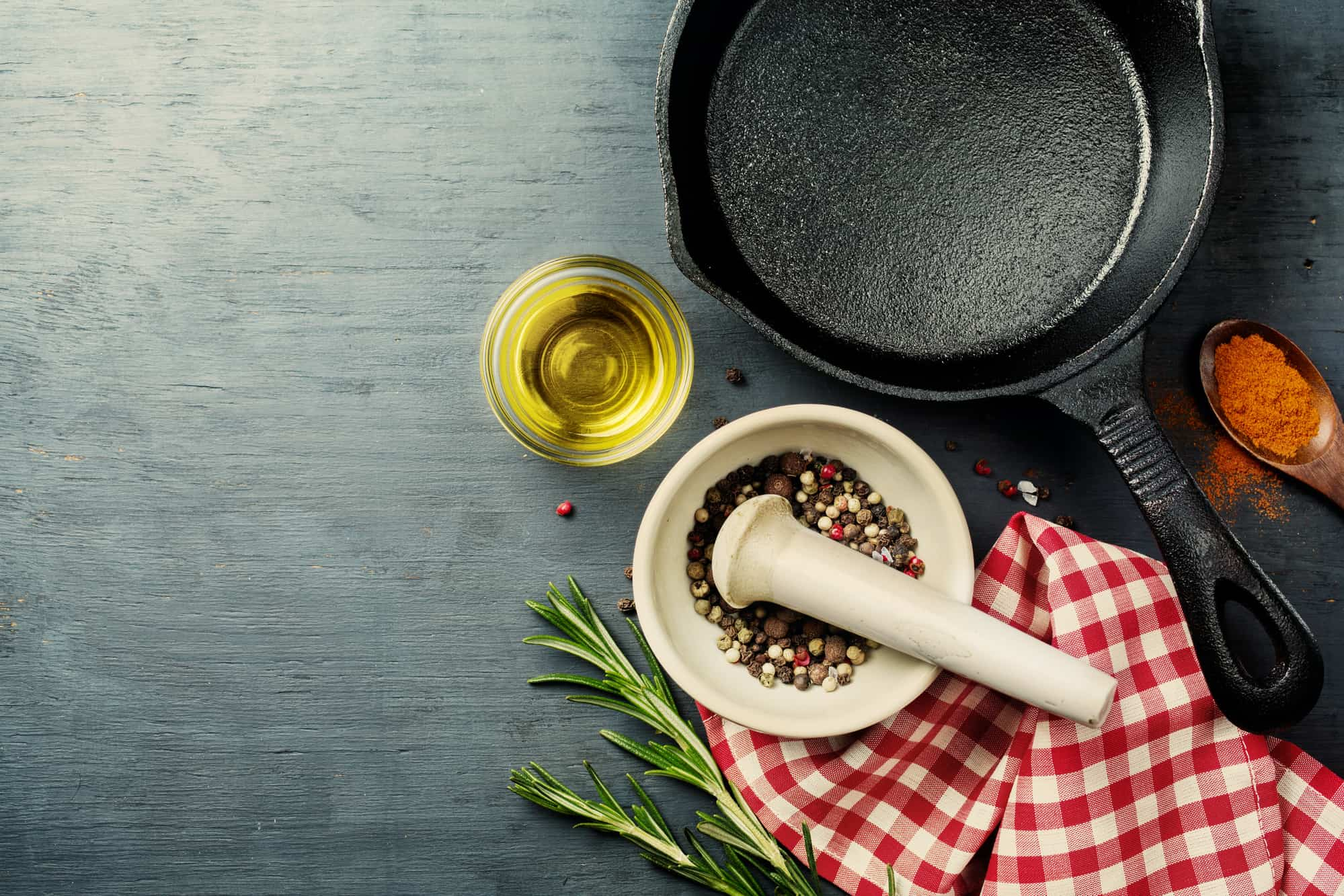 food background with cast iron skillet, herbs and spices selection