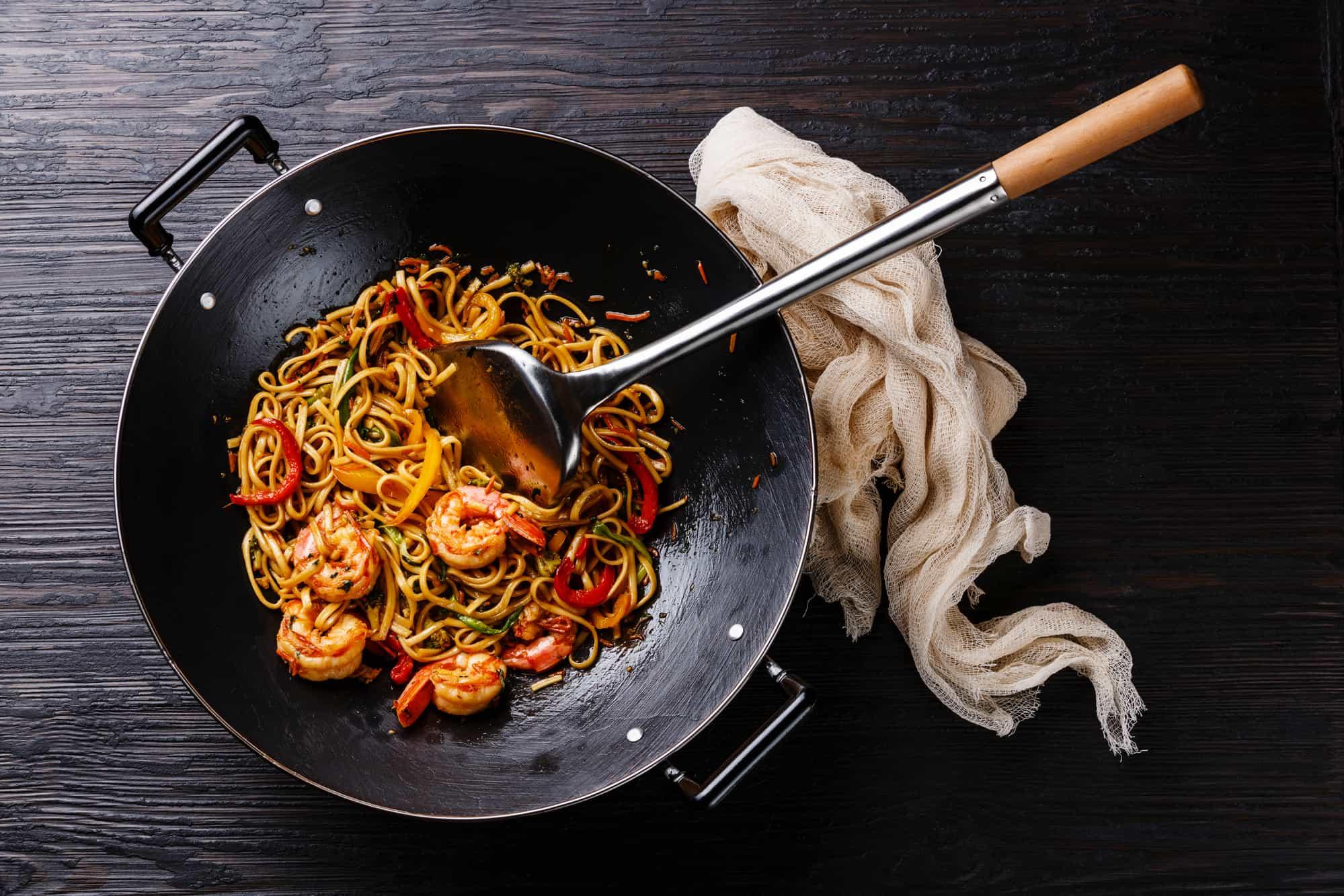 Udon stir fry noodles with prawn shrimp and vegetables in wok pan on black burned wooden background