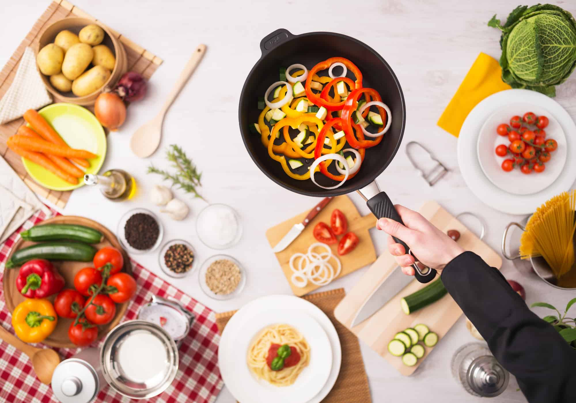 Professional cook frying fresh sliced vegetables in a nonstick pan hands close up, food ingredients and kitchenware on background