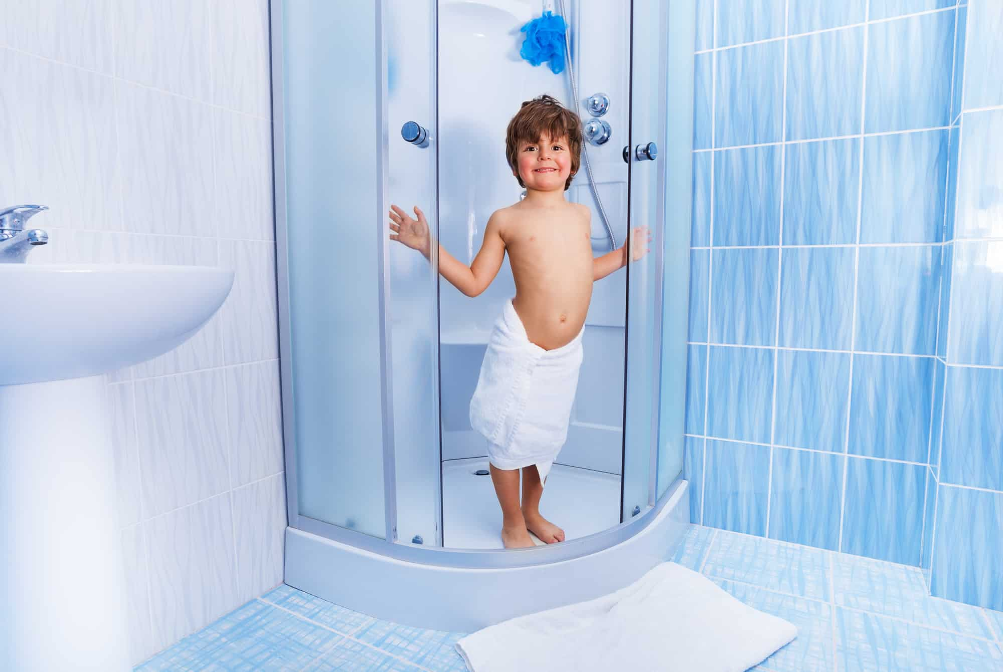 Little happy 4 years old boy opens doors in the hotel shower covered in white towel and smiling