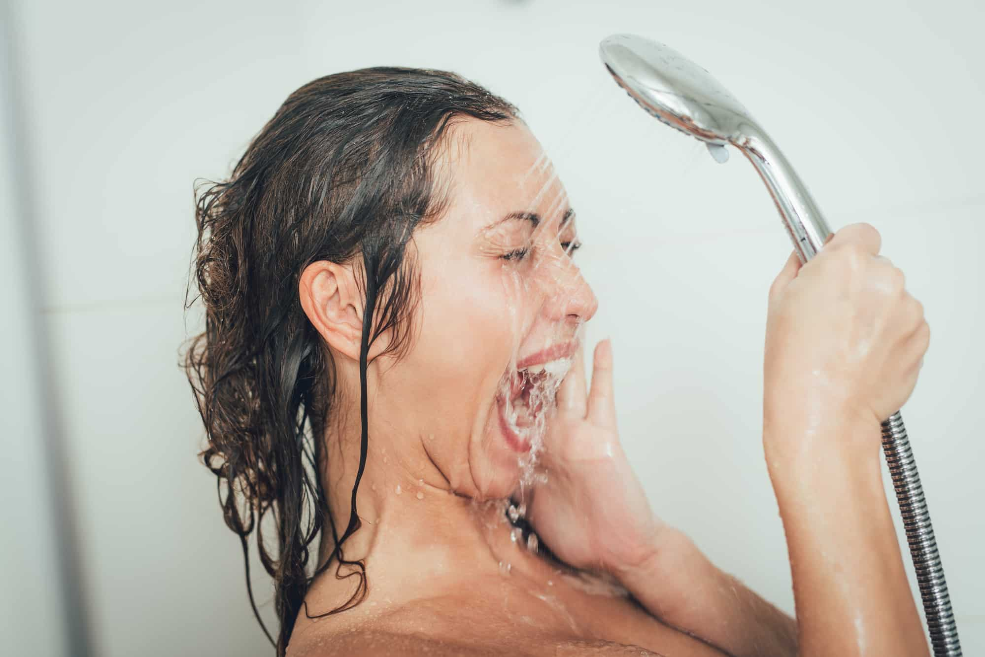 Beautiful cheerful girl washing face with water in shower cabin in while showering.