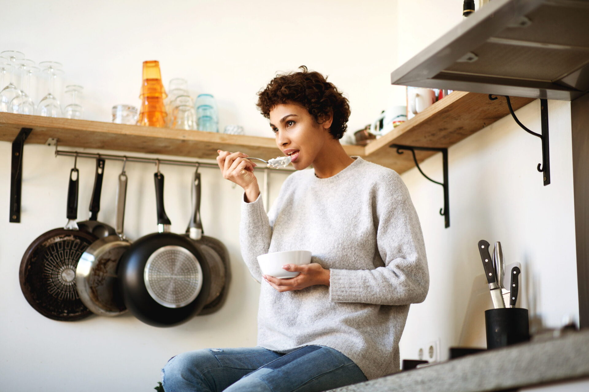 woman sitting on kitchen counter eating yogurt