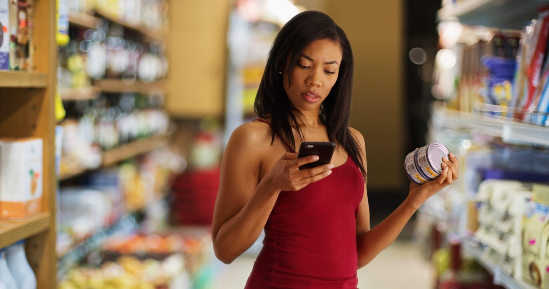 Black woman studies her phone at the grocery store