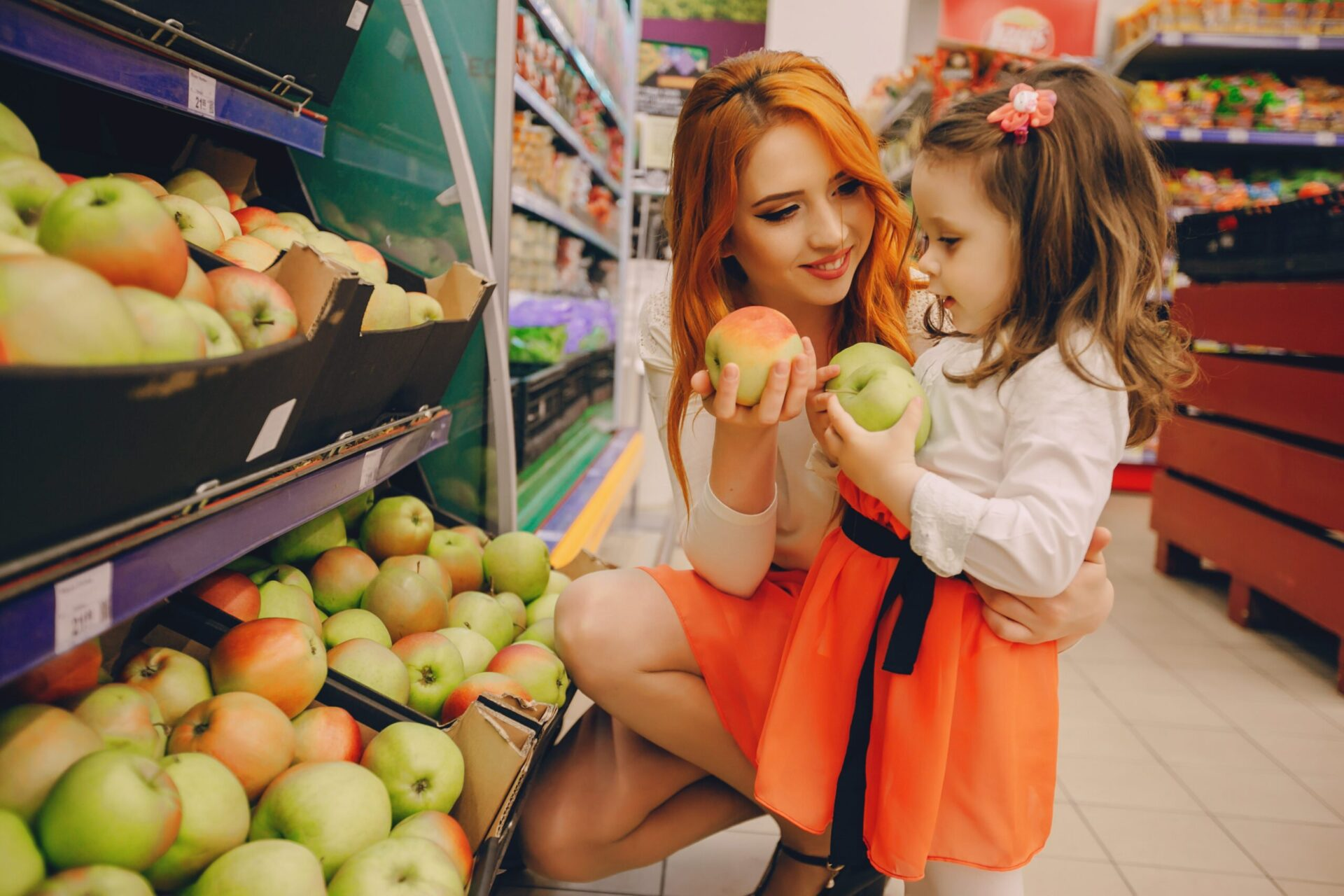 beautiful young red-haired mother with little daughter buying groceries and products in the supermarket