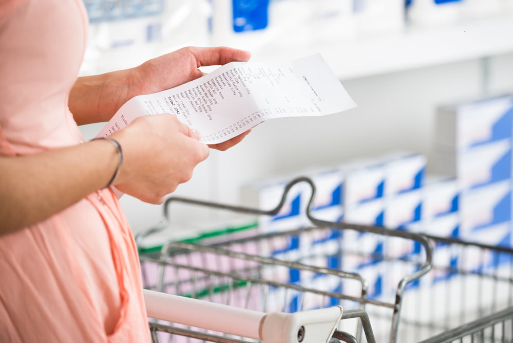 Midsection of young woman holding receipt in supermarket