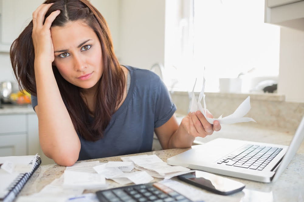 Young woman looking worried over finances in kitchen