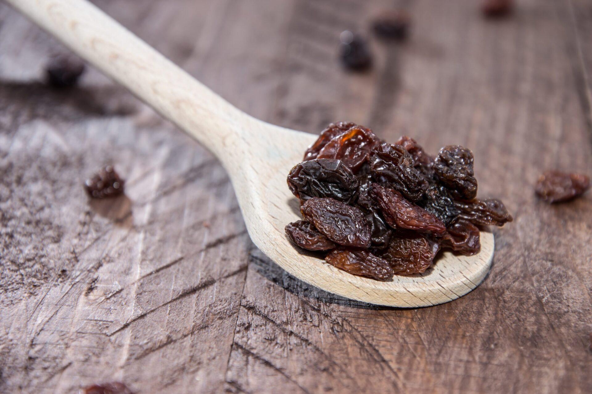 Raisins on a wooden spoon on wood