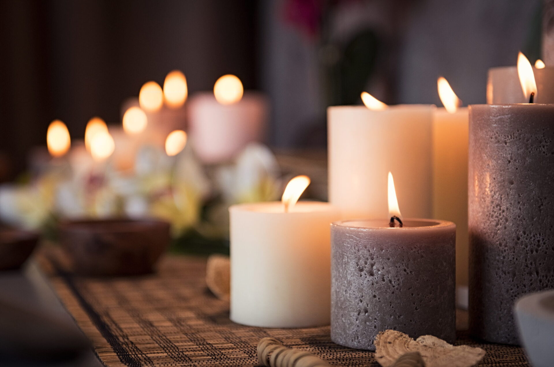Closeup of burning candles spreading aroma on table in a spa room. Beautiful composition with grey and white candles for spa treatment