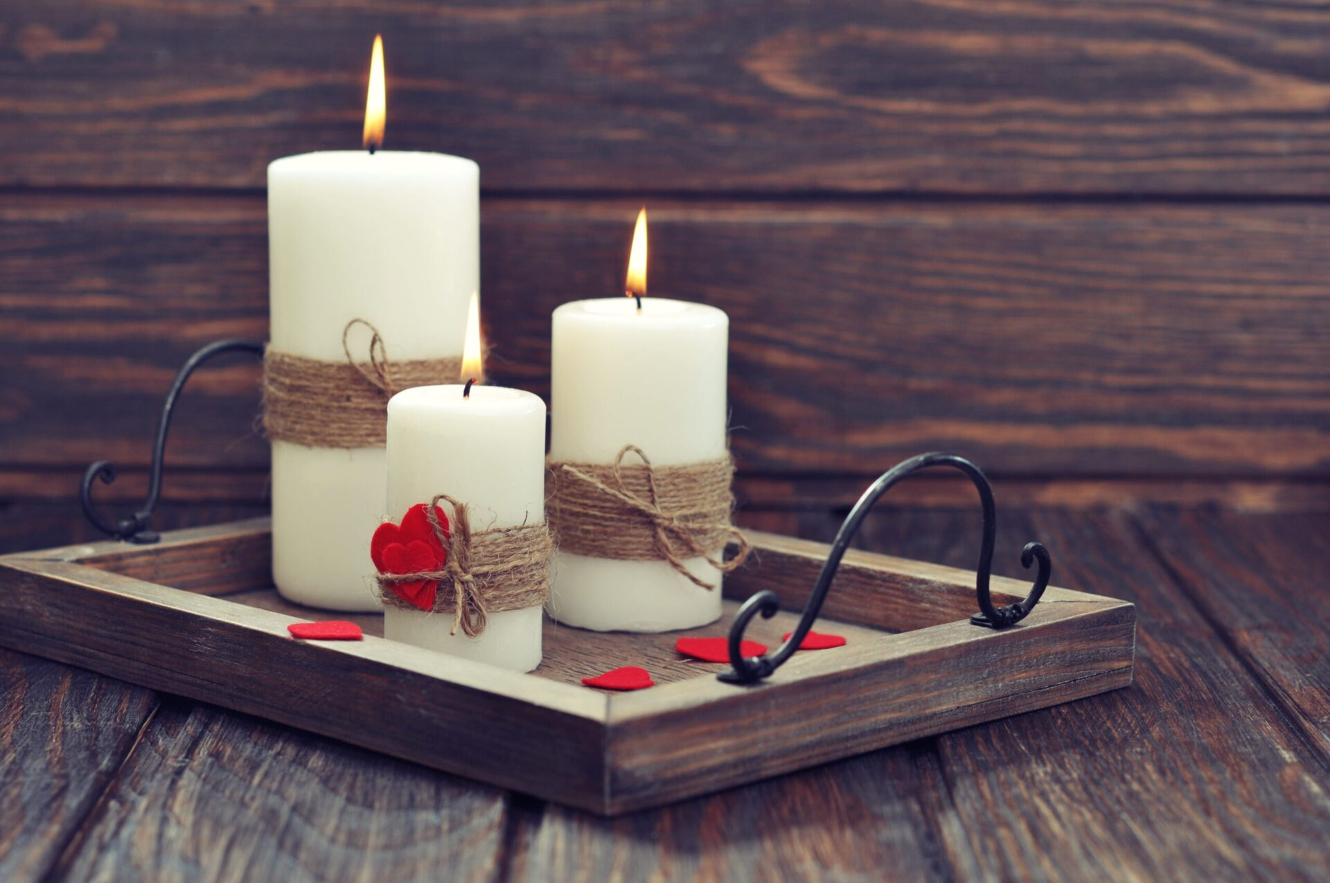 Candles on vintage tray with fabric hearts on wooden