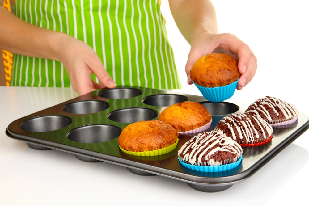 Preparing tasty muffin cakes close up on nonstick bakeware