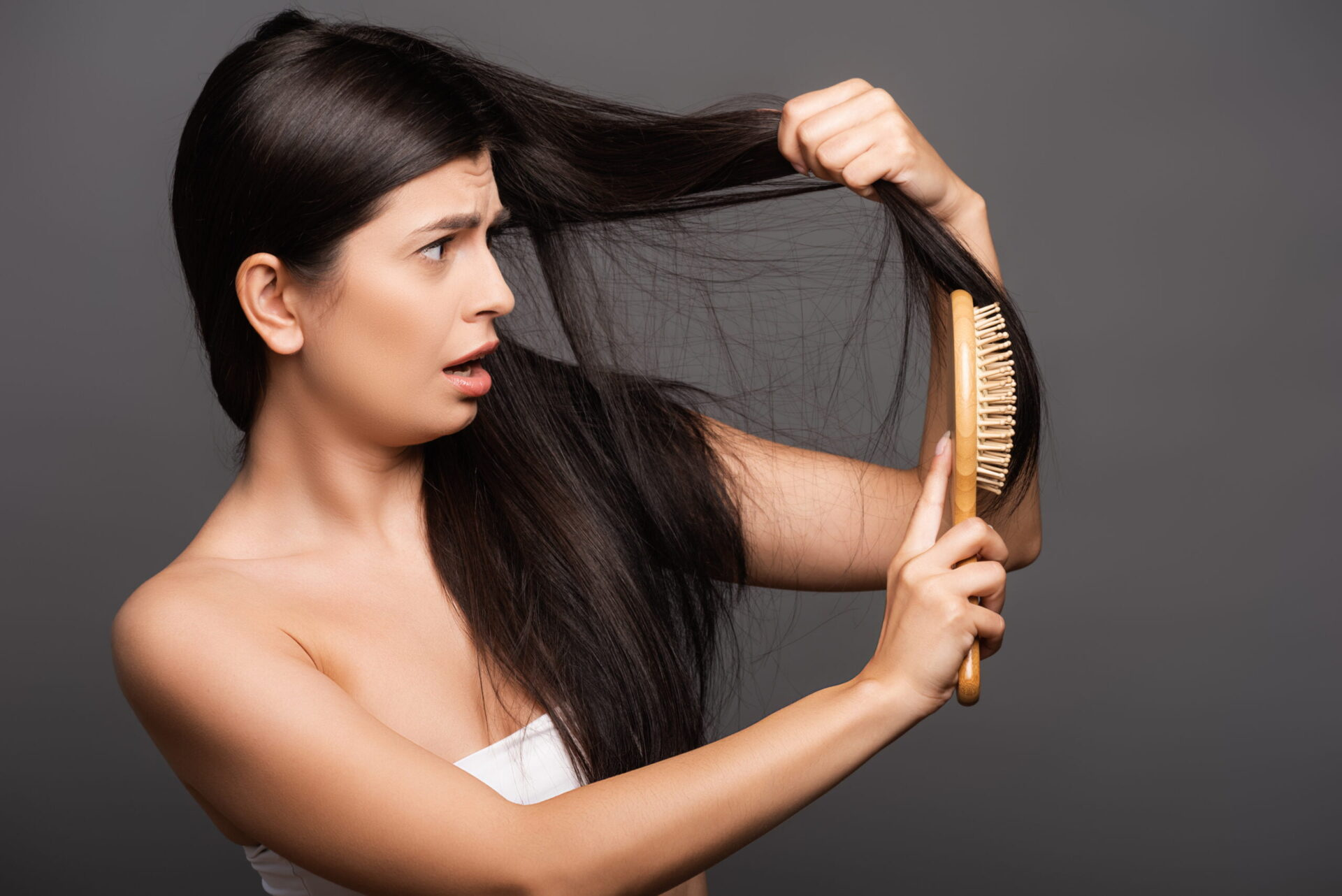 Latino woman looking at her oily hair that needs dry shampoo