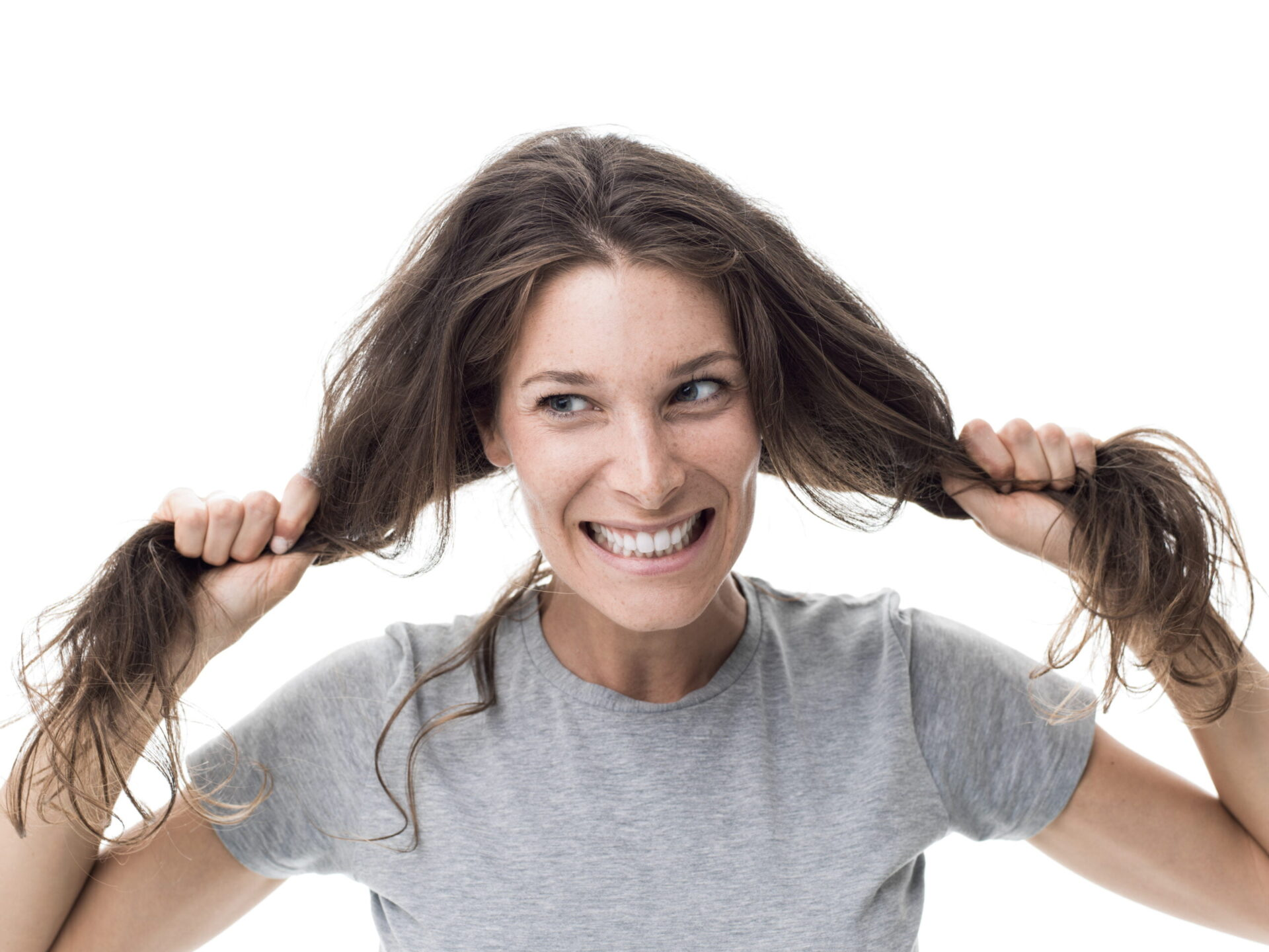 Angry woman having a bad hair day, she is pulling her messy and tangled hair