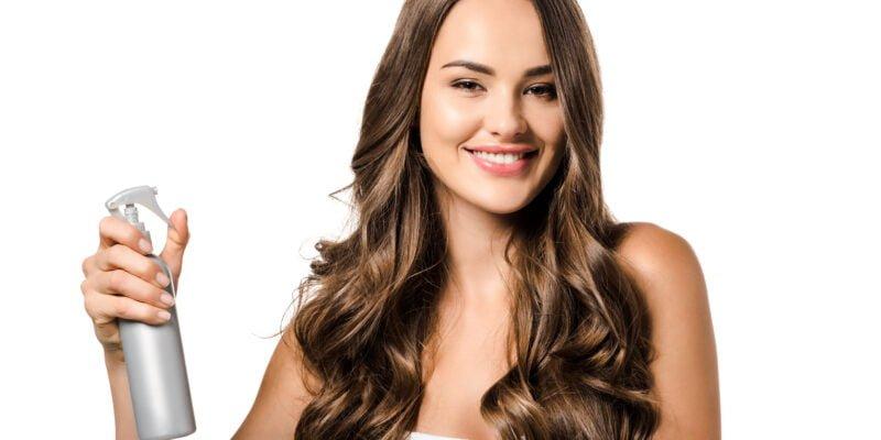 woman spraying organic dry shampoo on her hair