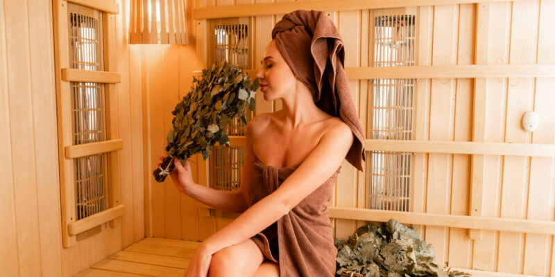 Young woman relaxing in a sauna dressed in a towel. Interior of new Finnish sauna, infrared panels for medical procedures, classic wooden sauna