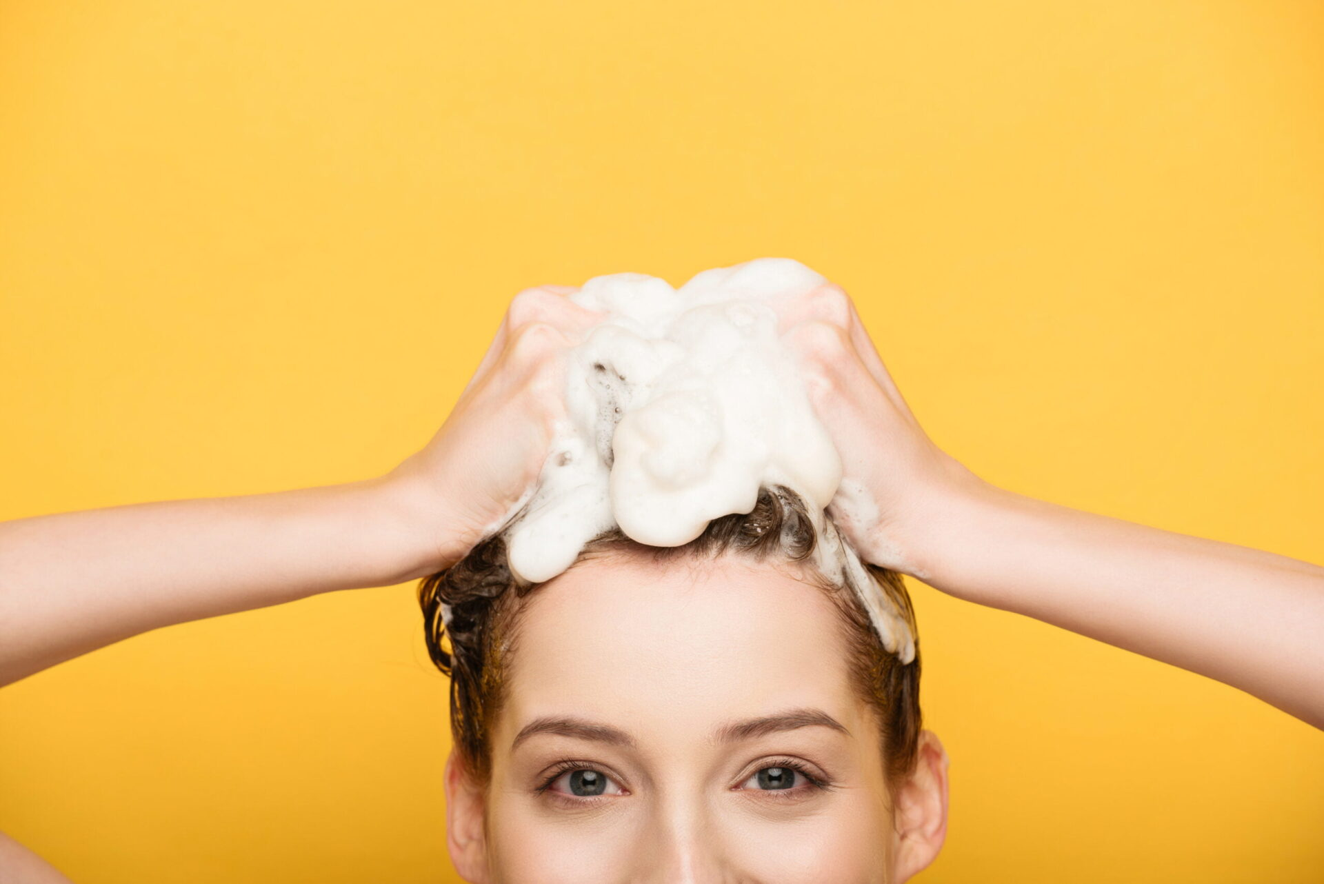 Woman washing her hair on yellow background