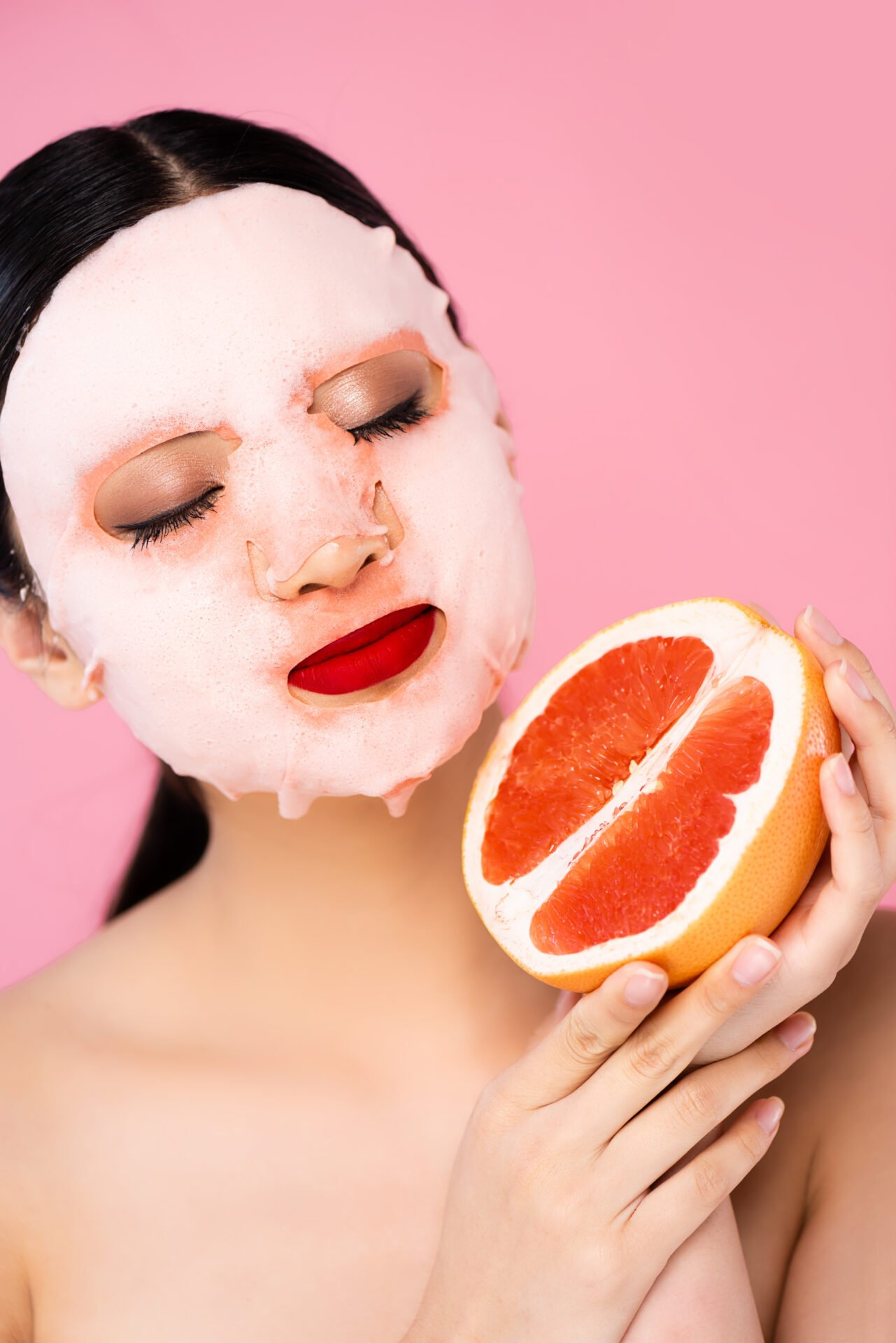 Korean woman with a non-toxic k-beauty face mask holding a grapefruit