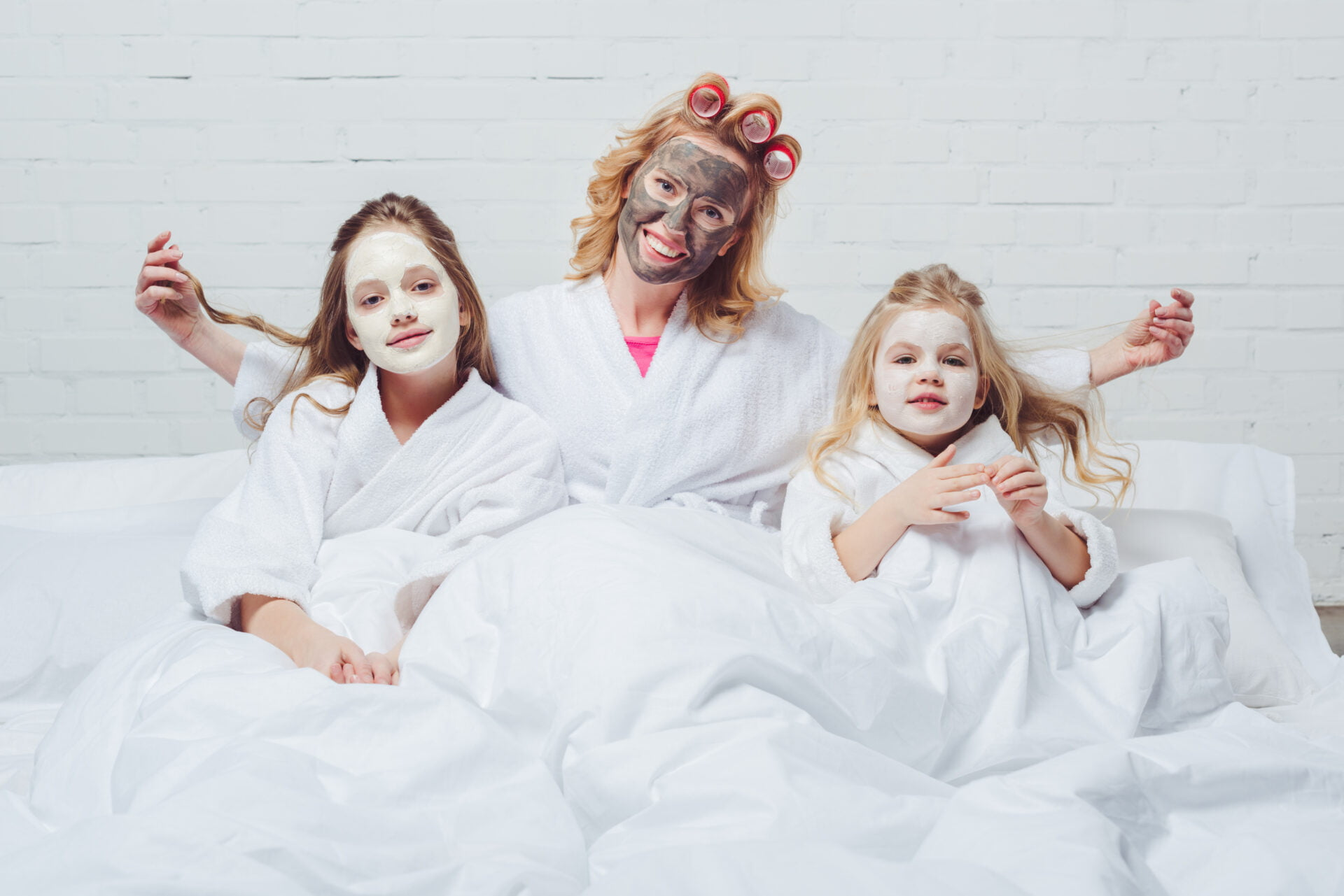 Mother with two daughters having a peel-off face mask slumber party