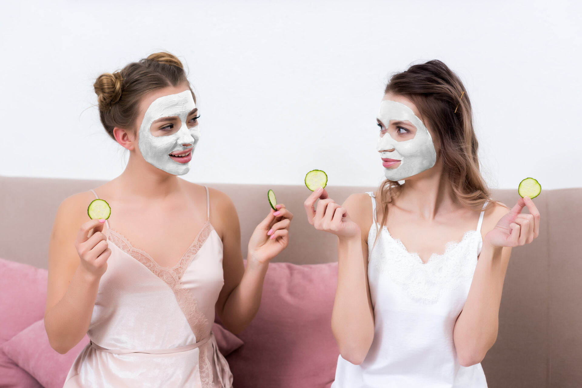 Women sitting together with pull off face masks and cucumbers for their eyes