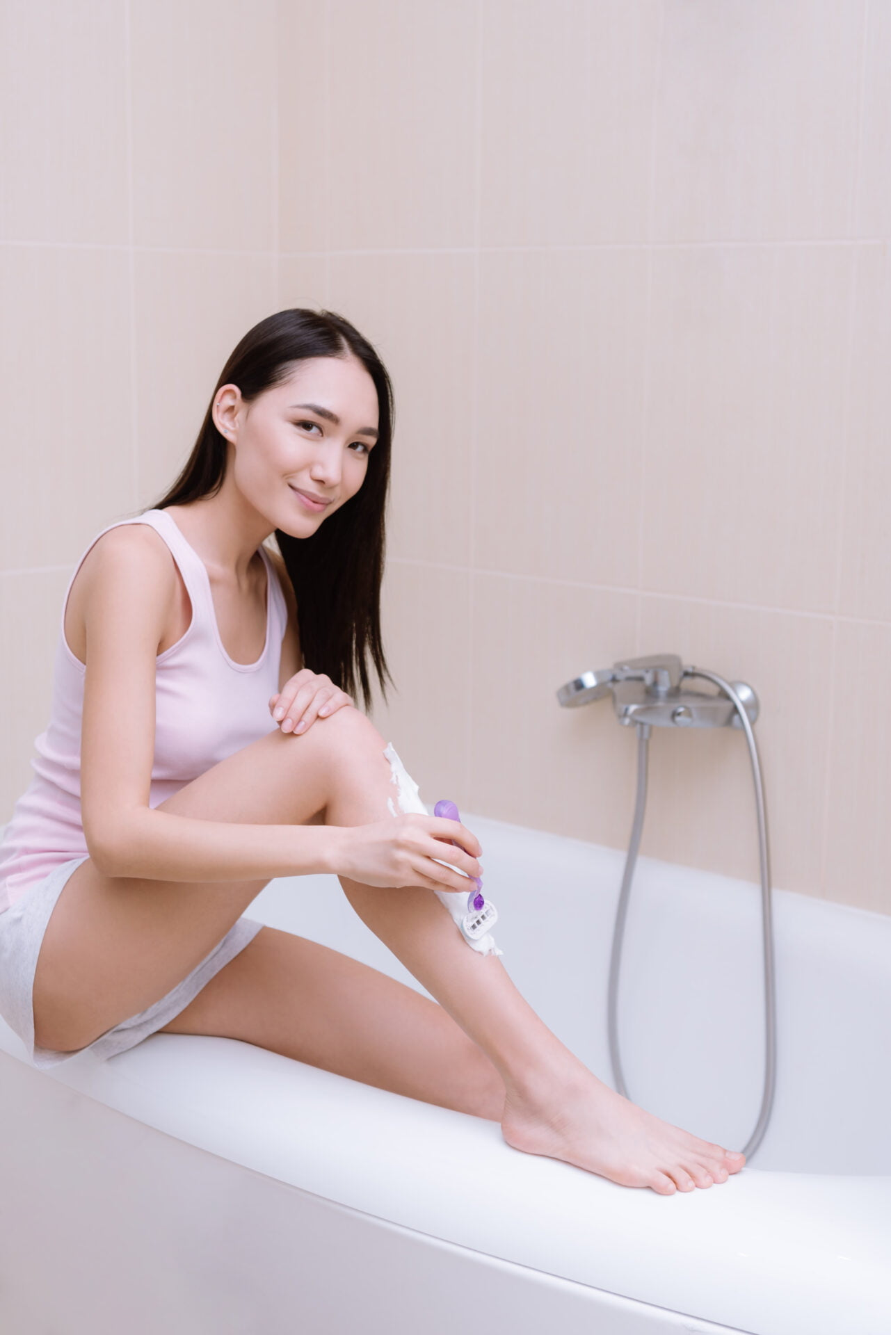 beautiful asian woman shaving her legs in bathtub