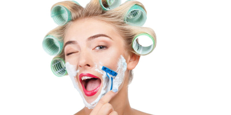 Cheerful woman has having cream over her face. She is shaving herself with razor. The girl is winking and laughing