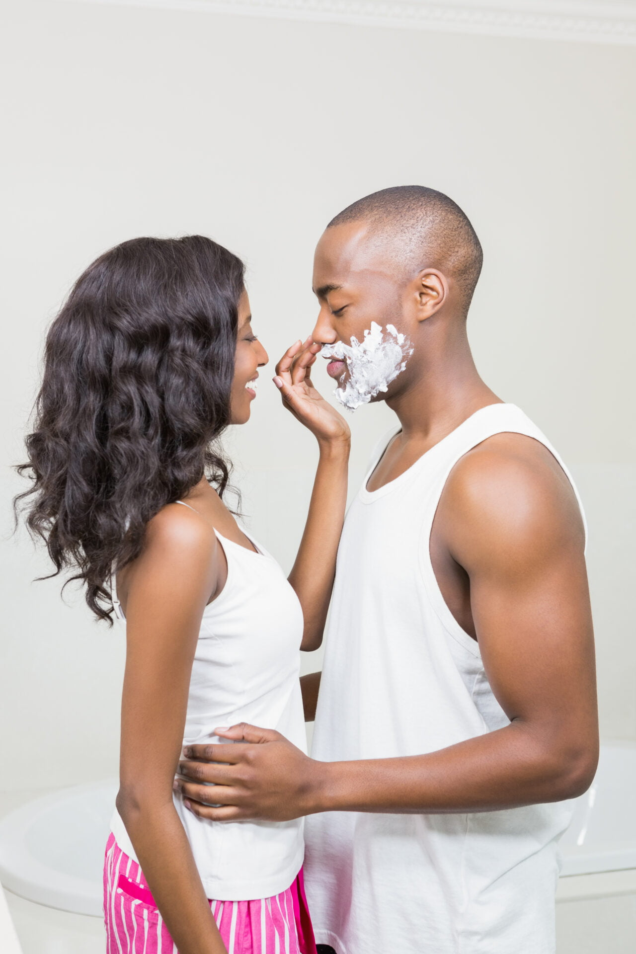 Young woman applying shaving cream on young mans face in the bathroom