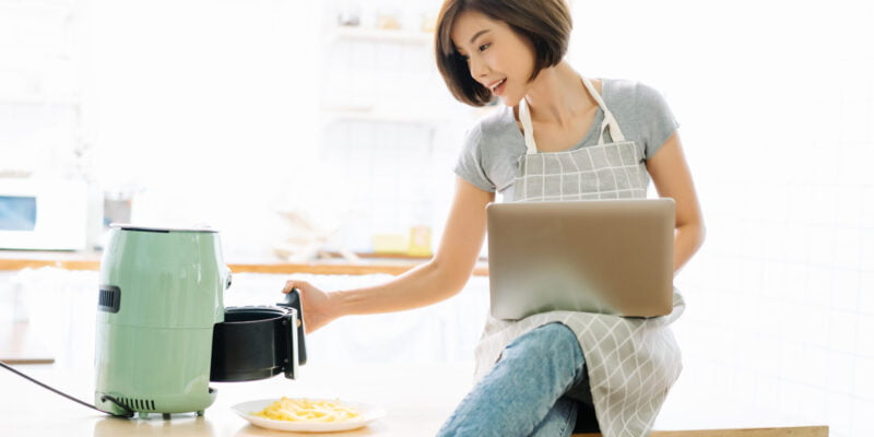 Portrait of beautiful Asian woman working on laptop while cooking with Air Fryers in kitchen