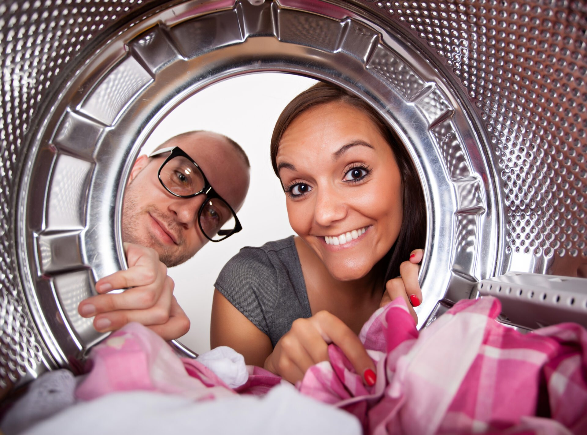 woman and man pulling clothes out of dryer