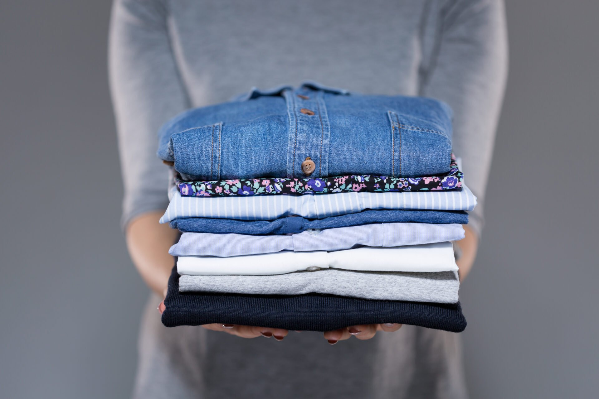 Woman holding folded clothes in hands